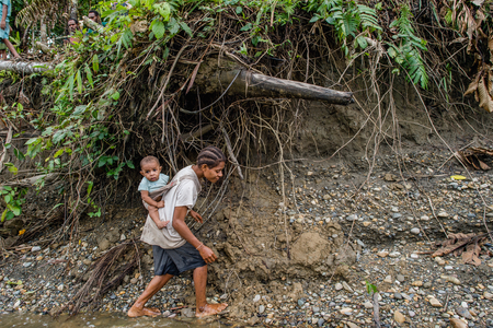 SITAK-MITAK SUBDISTRICT, ATSY DISTRICT, ASMAT, NEW GUINEA, INDONESIA - MAY 23: Papuan woman carrying child on her back on the Brazza river coast. Jjungle of New Guinea.Indonesia. May 23, 2016