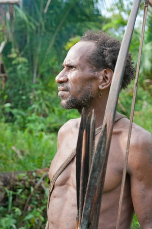 ONNI VILLAGE, NEW GUINEA, INDONESIA - JUNE 23: The Portrait Korowai man hunter with arrow and bow. Tribe of Korowai (Kombai , Kolufo).On June 23, 2012 in Onni Village, New Guinea, Indonesia Editorial