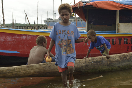 WEST PAPUA, NEW GUINEA, INDONESIA - JUNE 15 2016:  Three unidentified village kids playing with a standing boat on the shore side. Editorial