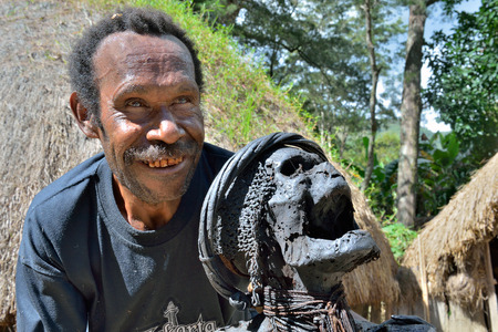 Wamena, Indonesia - May 14 2016: A man from the of Dani tribe shows the sacred mummy of a great ancestor. The mummy of the legendary tribe warrior, near Wamena town in Baliem Valley.
