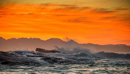 Marina. Nubes en un cielo rojo del amanecer, olas rompiendo con salpicaduras contra piedras, siluetas de montañas en el horizonte. Bahía falsa. Sudáfrica.