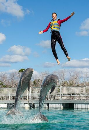 Woman pushed out of the water by dolphins, swimming with dolphins.