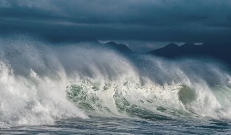 Seascape. Powerful ocean wave on the surface of the ocean. Wave breaks on a shallow bank. Stormy weather, stormy clouds sky background.