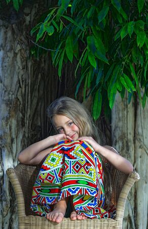 Little beautiful girl  at tropical tree  background. Portrait of cute child ready for tropical vacation.
