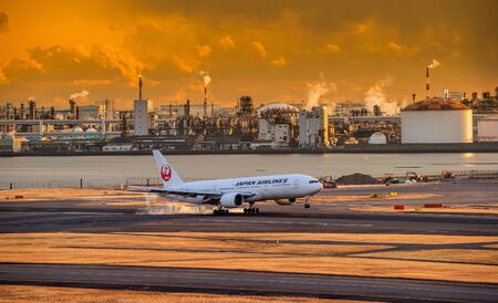TOKYO, JAPAN - February, 8, 2018. Japan Airlines or JAL plane landed at Haneda International Airport. In the Morning sun Yellow sky.