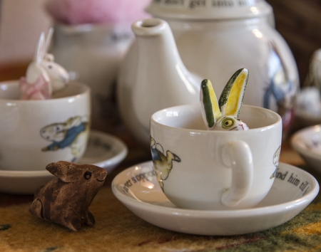Peter Rabbit Tea set with little rabbits poking around it  photo