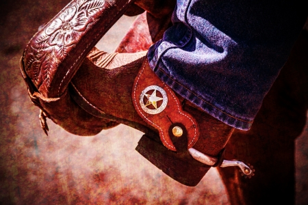 antiqued: Rustic looking cowboy boot with spur in stirrup with antiqued vignette.