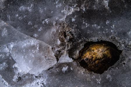 Frozen pond with cracks, bubbles, rocks and ice creating a network of textures and lines  photo