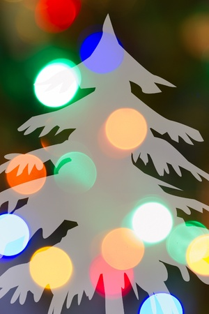 Silhouette of a snow-covered evergreen dominates a multicolored bokeh background in a vertical composition