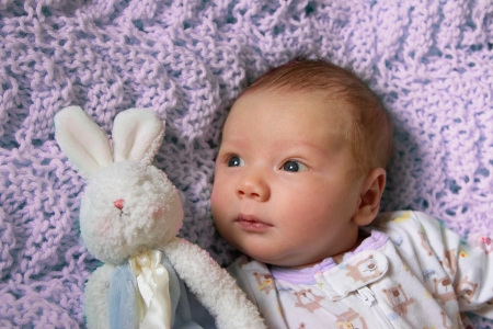 Close up of baby s happy face with bunny on pink background  photo