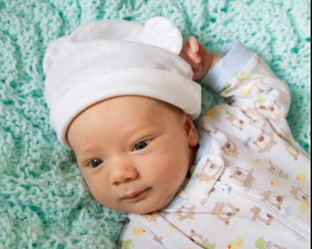 Close up of baby s happy face with smiling eyes wearing a funny hat  Stock Photo