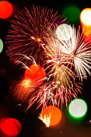 populate: Multicolored Bokeh lights and fireworks populate a night scene in a vertical background.
