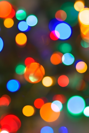 populate: Multicolored Bokeh lights populate a night scene in a vertical background. Stock Photo