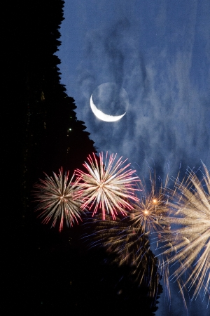whimsey: Quarter moon and fireworks against a dramatic night sky in a mountainous landscape. Stock Photo