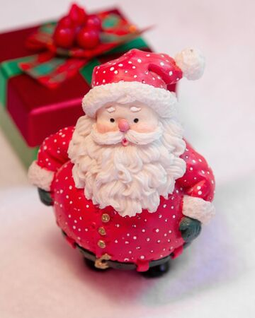 whimsey: A fat little red Santa Claus stands in front of a gift on white background  Stock Photo
