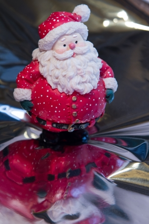 whimsey: A fat little red Santa Claus stands in front of a gift on reflective surface