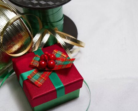 whimsey: Little red and green Christmas gift with green and gold ribbon  resting on soft white background with copy space  Stock Photo