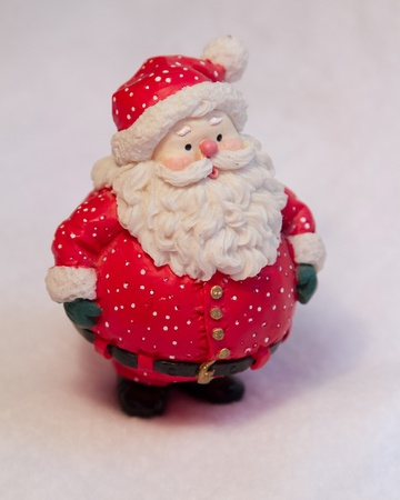 whimsey: A fat little red Santa Claus stands on vertical white background