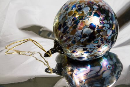 Multicolored glass ornament rests on reflective mylar with copy space