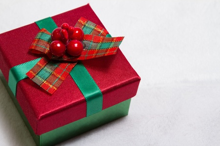 Little red and green Christmas gift resting on soft white background with copy space Stock Photo - 17101720