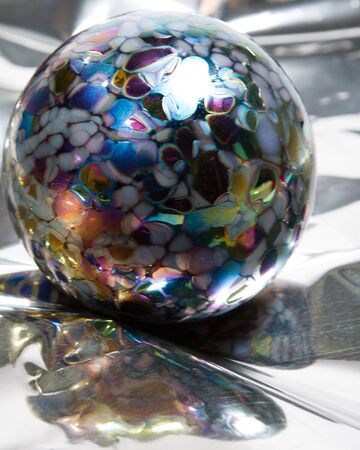 Multicolored glass ornament rests on reflective mylar with copy space  Stock Photo - 17101714