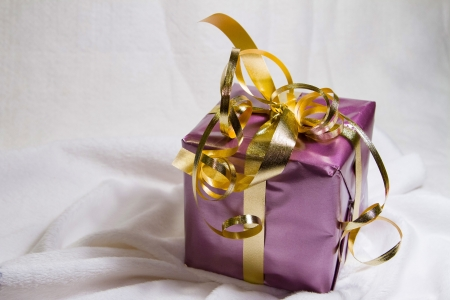 Pretty gift wraped in purple and gold resting on soft white surface