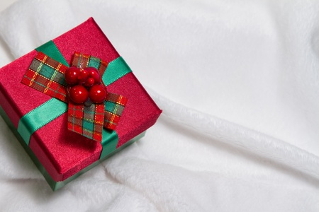 whimsey: Little red and green Christmas gift resting on soft white background with copy space  Stock Photo