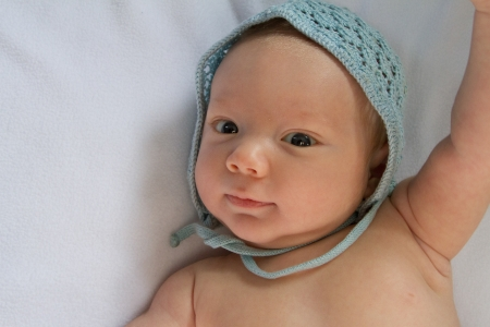 whimsey: Close up of happy baby wearing hand-crocheted blue cap.