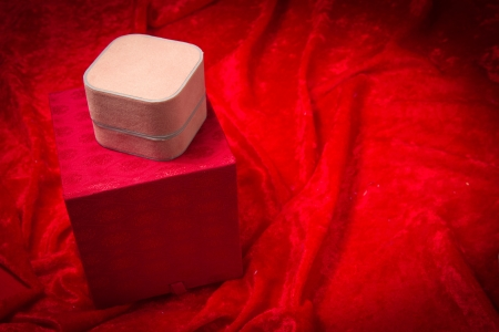 A variety of luxurious red jewelry boxes stacked on velvet background