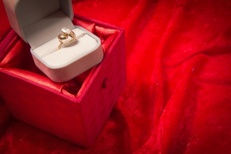 Diamond ring rests in opened jewelry box on red velvet background  photo