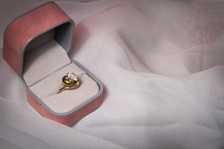 Diamond ring rests in opened jewelry box on white background