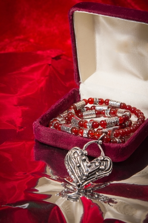 Silver and red stone necklace cascades from jewelry box on red velvet background  photo