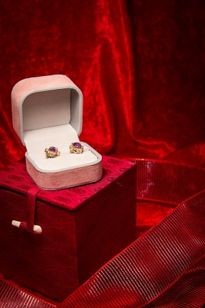 Pair of earrings rest in open jewelry box on red velvet backgound  photo