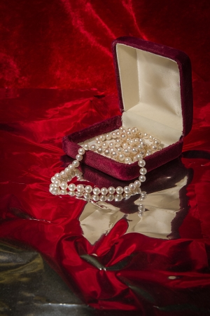Pearl necklace cascades from jewelry box on red velvet background