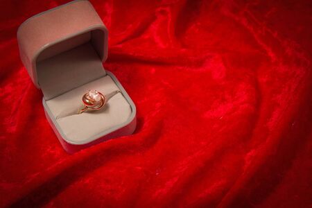 Diamond ring rests in opened jewelry box on red velvet background.