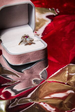 Ring rests in open jewelry box on red velvet backgound.