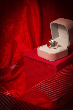 Ring rests in open jewelry box on red velvet backgound. photo