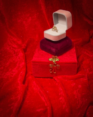 Diamond ring rests in opened jewelry box on red velvet background. photo
