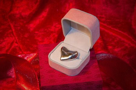 Silver heart rests in open jewelry box on red velvet backgound. photo