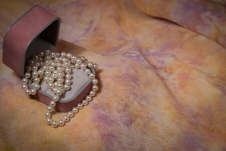 Pearl necklace cascades from jewelry box on pink and yellow pastel background. photo