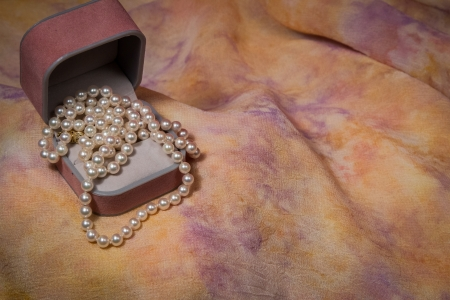Pearl necklace cascades from jewelry box on pink and yellow pastel background.