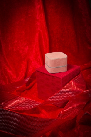 A variety of luxurious red jewelry boxes stacked on velvet background. photo