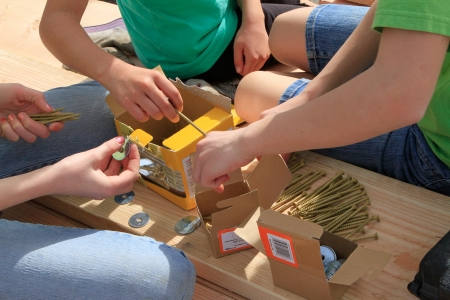 Children work as a team to assemble screws and nuts for construction project.
