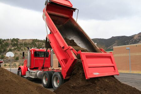 Big red dump truck dumps pile of dirt. Editorial