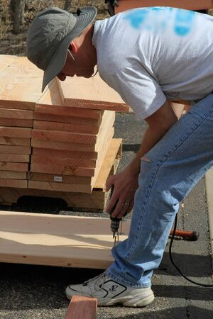Man drills into wood at construction site Editorial