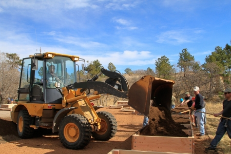 Raised garden beds are being prepared by team of people and front-end loader.