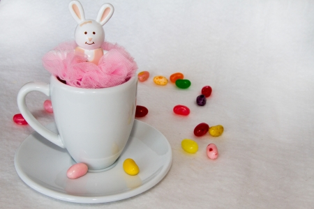 Bunny in pink tutu peeks out of a white expresso cup with jelly scattered around in horizontal composition