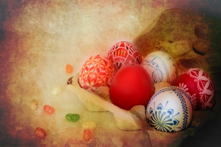 Colorful Easter eggs sit in a carton with jelly beans scattered around with golden texture overlay