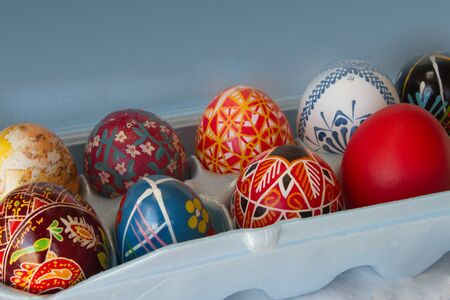 Colorful Easter eggs sit in a blue carton in diagonal composition with copy space  Stock Photo