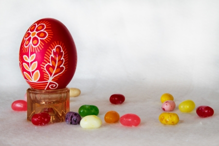 A decorated red Easter egg stands next to jelly beans on a white background in horizontal composition